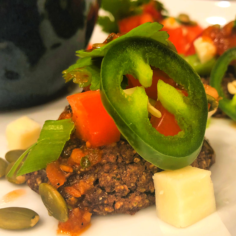 Black Bean Cakes topped with veggies, pepitas, and cotija