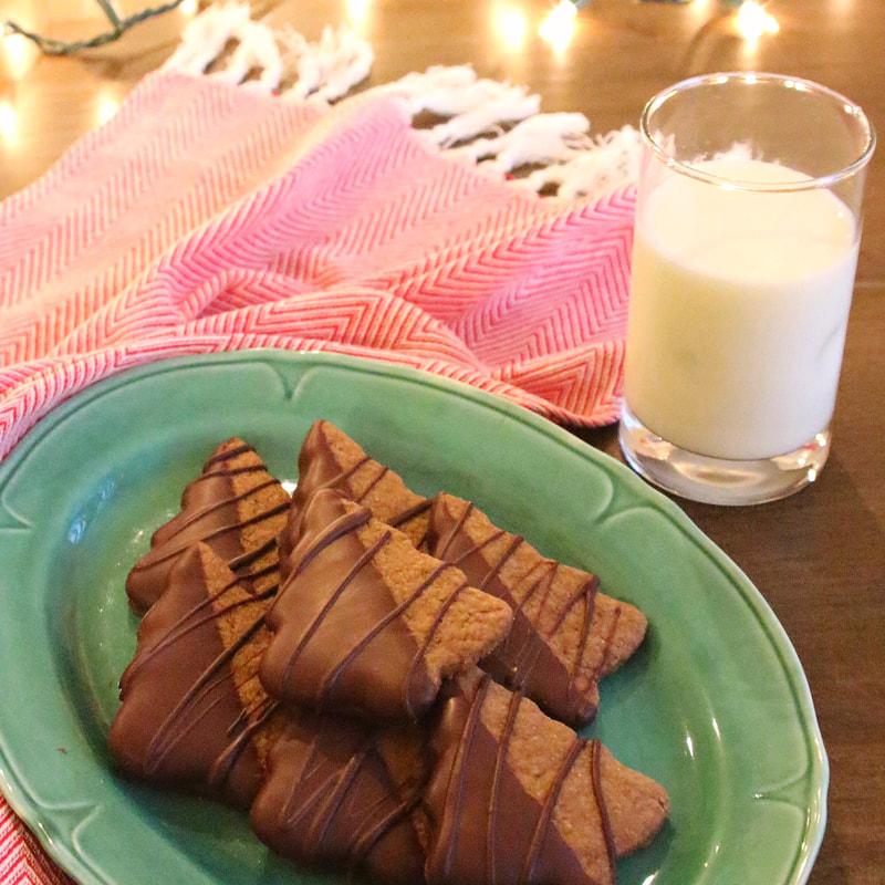 Chocolate-dipped gingerbread tree cookies on a green plate with a glass of milk on a red and white kitchen towel with Christmas lights in the background