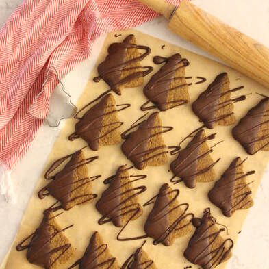 Chocolate-dipped gingerbread tree cookies on a piece of parchment surrounded by a red and white kitchen towel, tree cookie cutter, and wooden rolling pin