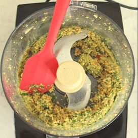 Minced and blended bell peppers, onions, garlic, cilantro, and oats in food processor bowl