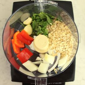 Bell pepper, garlic cloves, cilantro, oats, and onion in food processor bowl fitted with standard blade