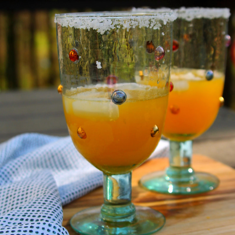 Smoky Orange Margaritas sitting on a outdoor table